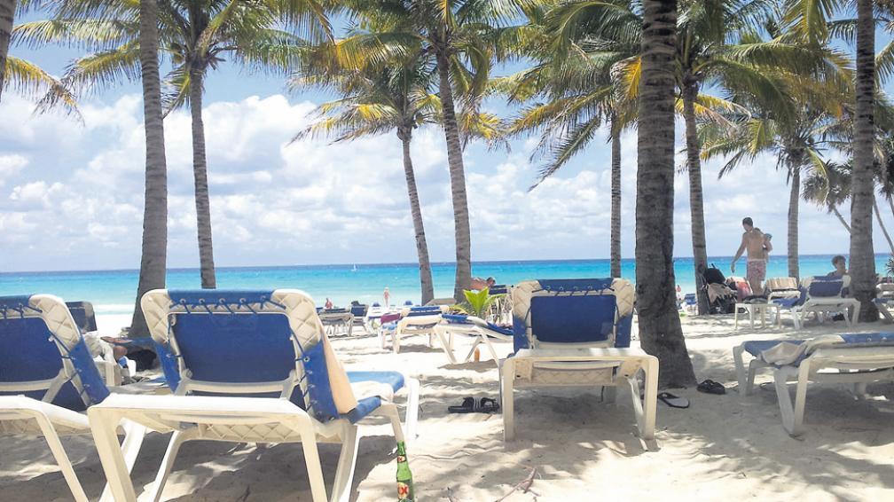 Arenas doradas, palmeras y el horizonte de tonos turquesas del Caribe mejicano. Playa del Carmen.