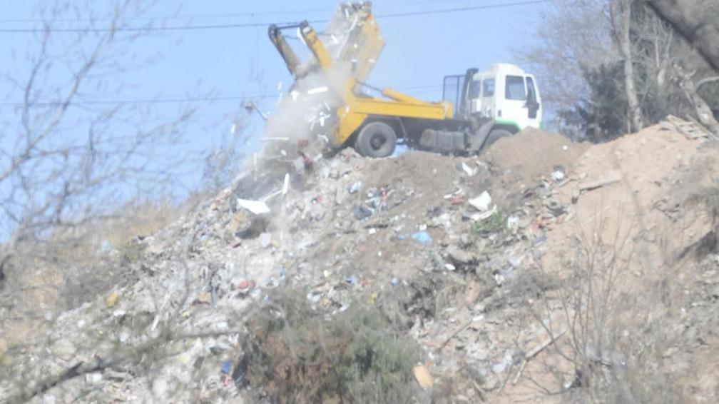 Descarga. El camión vacía el contenedor sobre la barranca (Martín Baez).