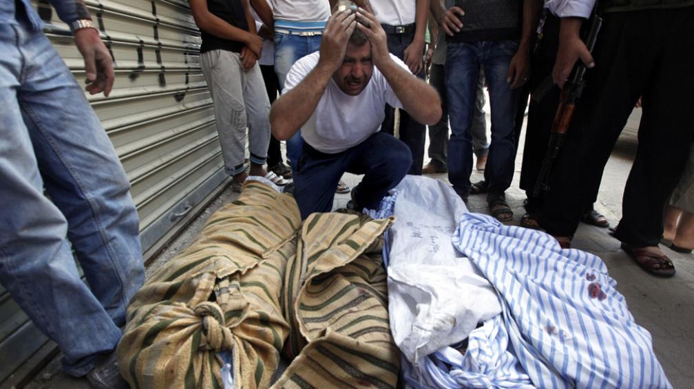 Dolor. Un hombre llora ante los cuerpos de cuatro familiares muertos en Alepo (AP).