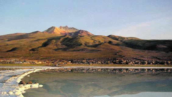 De un lado, las montañas y el volcán Thunupa; del otro lado, el salar con su espejo que invierte las imágenes, y al medio, Coqueza.