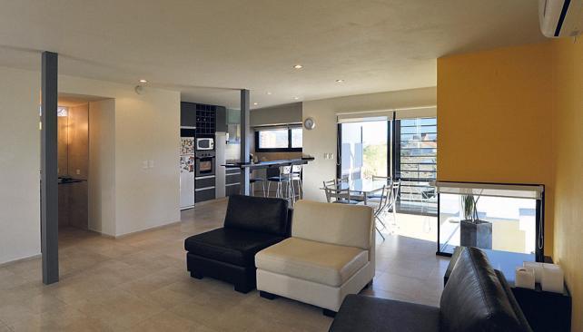 En un solo ambiente, sectorizado con el equipamiento, se ubican la cocina, el comedor y el estar (Roger Berta).