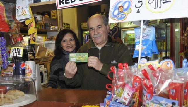 Afortunado. Víctor muestra el cartón ganador, junto a su pareja, en el quiosco que ambos atienden (La Voz / Pedro Castillo).