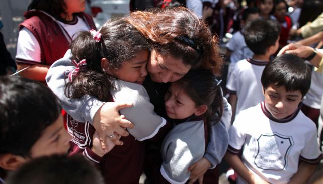 MÉXICO. Una mujer calma a los niños asustados por el fuerte temblor (AP).