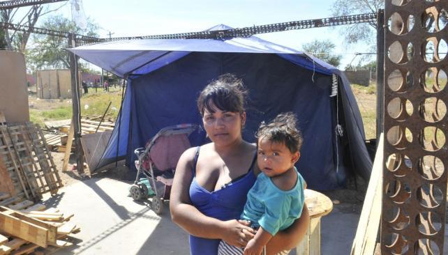 """Pamela Agüero. """"Armé una carpa y me vine a vivir con mi marido y Tiziana, de 9 meses. Ojalá pueda conseguir un pedazo de tierra para levantar algo propio"""" (Ramiro Pereyra / La Voz)."""