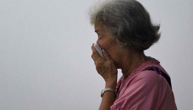 Fumigação.  Uma mulher cubana cobre o rosto, na sequência de um caminhão exterminador para eliminar mosquitos em Havana (AP).
