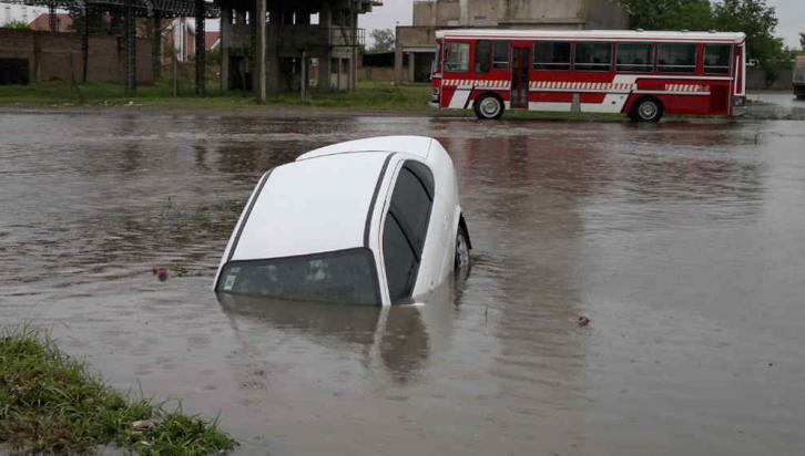 """JUAN B. JUSTO. Un auto se """"clavó"""" en un bache y el agua lo tapó (Raimundo Viñuelas)."""
